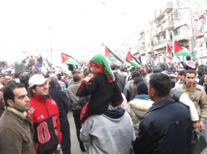 2 guys wave to a little girl wearing traditional garb and sporting a Palestinian flag scarf.