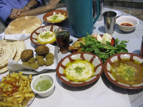 "Our breakfast at Hashem's.  Clockwise from the top: Green plastic water pitcher, communal steel drinking cup, red peppers, ""veggie tray"" (in middle) including raw onions tomatoes and mint, a bowl of fool (bottom right), a bowl of hummus, green citrus/pepper sauce, french fries,  falafil (the larger ones have onions, and sesame seeds), pita bread, glass of tea.  $4.50 for two people!  Ramadan Kareem!"