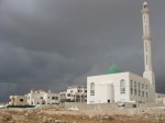 Storm rolls in behind green and white mosque
